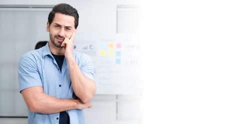 Confidence team leader. Young man owner startup business thinking and looking at camera with smile while his colleagues working in the background Stockfoto
