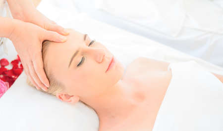 Beautiful woman receiving head and facial massage in spa salon. Concept of body health care and traditional thai massage relax Archivio Fotografico