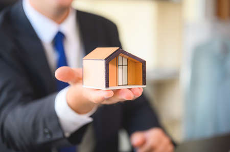 Property investment and house mortgage financial concept. Business man showing home model Archivio Fotografico