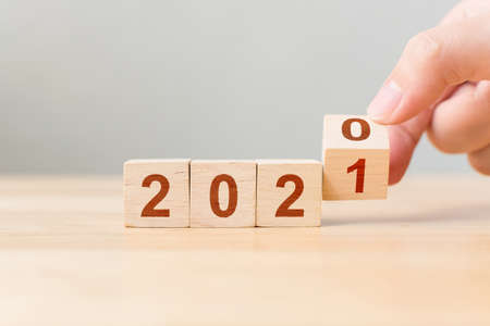 New year 2020 change to 2021. Hand flip over wooden cube block. New year resolution goal concept Archivio Fotografico