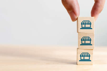 Franchise business marketing system concept. Structure service store network strategy. Hand putting wooden block on top with icon store Archivio Fotografico