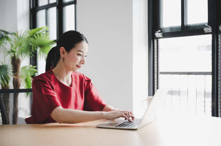 Work from home concept, Portrait of beautiful young asian woman working on laptop in workplace Archivio Fotografico