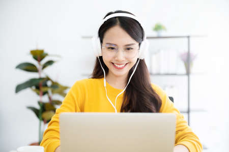 Young asian woman in headphone having conversation chatting while using laptop at house. Work at home, Video conference, Online meeting video call, Virtual meetings, Remote learning and E-learning Archivio Fotografico