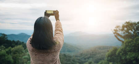 Asian woman take a photo by smartphone on mountain in thailand. She wear sweater and glove