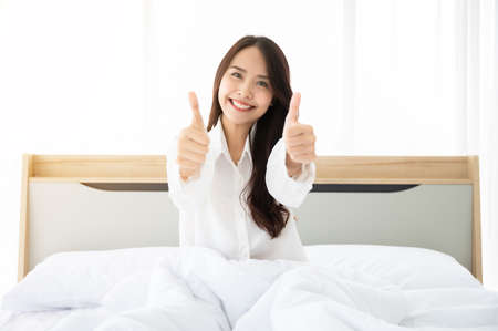 Beautiful women asian wake up in morning in bedroom. She clothing white dress and thumb up meaning good better