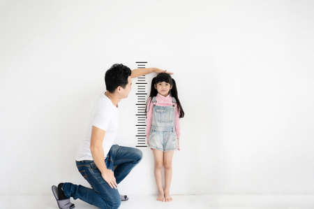 Dad measures growth of her child daughter at blank white brick wall Standard-Bild
