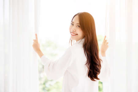 Young asian beautiful woman clothing white dress and open curtain window at morning in bedroom. She feeling happy and smile to camera