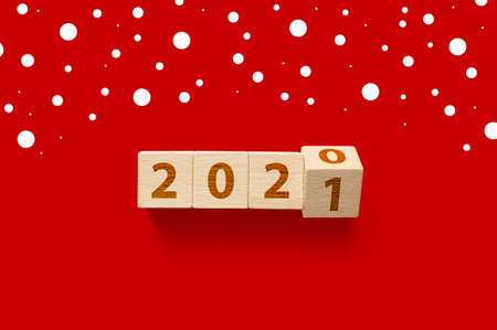 New year 2020 change to 2021 concept. Wooden cube block flip change year on red background