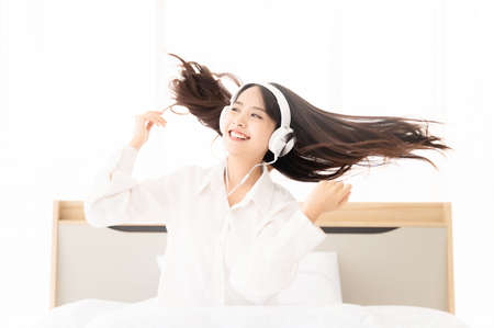 Beautiful young asian woman in headphones listening to music and dancing on bed at bedroom in morning time