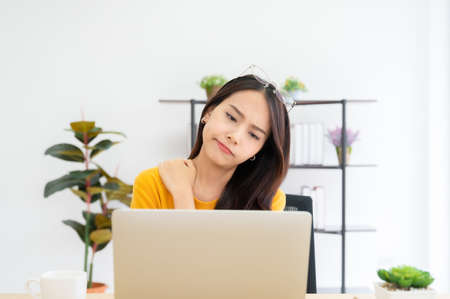 Office syndrome concept. Young asian woman feeling pain in neck and shoulder after working on computer laptop for a long time. She stretches to relax her muscles