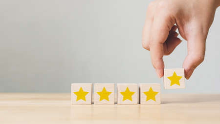 Hand putting wooden cube with five star shape on wood table with copy space. The best excellent business services rating customer experience concept