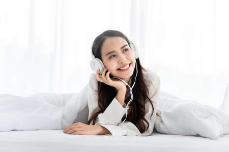 Beautiful young asian woman in headphones listening to music and lying down on bed at bedroom in morning time Standard-Bild