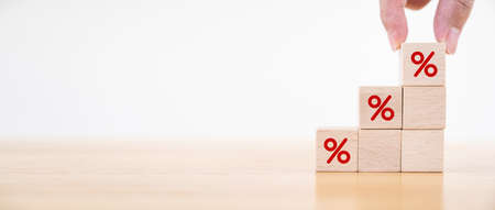 Interest rate financial and mortgage rates concept. Hand putting wood cube block increasing on top with icon percentage symbol upward direction. Panoramic image