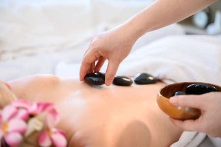 Spa hot stone thai massage beauty treatment.Young woman getting black hot stone on back her in spa salon Standard-Bild