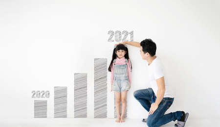 Dad measures height increase of her child daughter at white brick wall with graph growing growth year 2020 to 2021 Standard-Bild