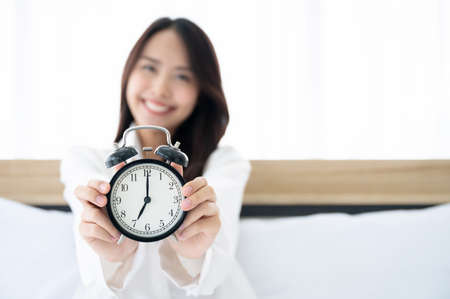Young asian beautiful woman wake up in the morning on bed. She clothing white dress and holding alarm clock