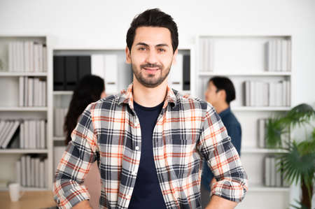 Young man asian confidence team leader business looking camera and smile in modern office room with blurred background group people