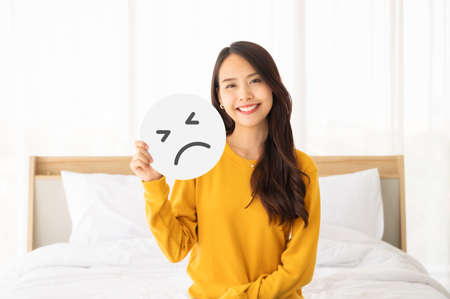 Asian beautiful woman happy and smile sitting on bed with holding paper sad emoticon symbol