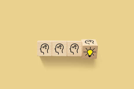 Concept creative idea and innovation. Wooden cube block with head human symbol and light bulb icon