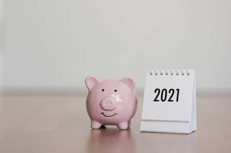 Calendar year 2021 and piggy bank on wooden floor. Concept finance business investment