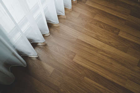 Laminate wood floor and white curtain decorating in room house Фото со стока