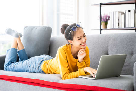 Young asian woman using laptop at house. Work at home, Video conference, Online meeting video call, Virtual meetings, Remote learning, E-learning and Online Education