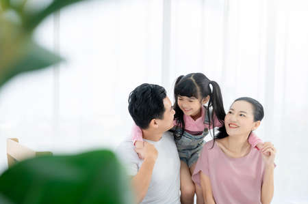 Happy asian family people leisure in bedroom together. Father and mother with daughter relaxing on bed and enjoy funny