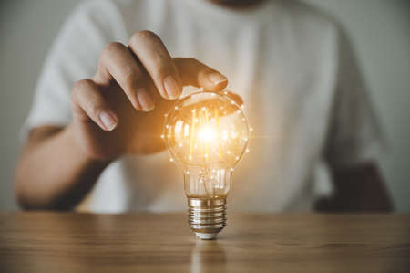 Hand holding light bulb on wood table. Concept of inspiration creative idea thinking and future technology innovation Standard-Bild
