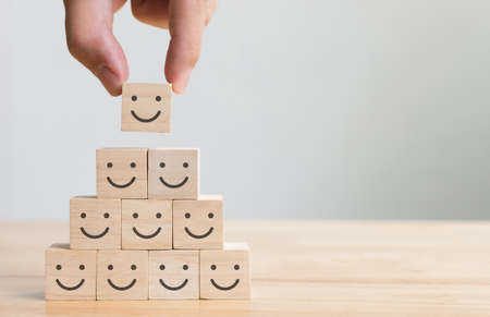 Hand putting wooden cube block shape with icon face smiley, The best excellent business services rating customer experience, Satisfaction survey concept