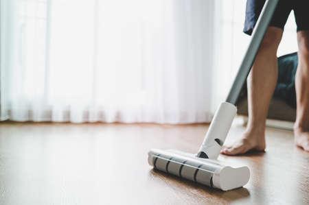 Barefoot man cleaning room by vacuum cleaner on laminate wooden floor. He doing homework cleaning routine. Housekeeping job concept 版權商用圖片