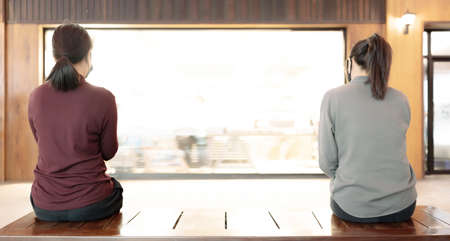 Woman two people in making social distancing sitting on bench in public 版權商用圖片