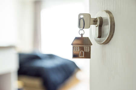 Open the door and door handle with a key and a keychain shaped house. Property investment and house mortgage financial real estate concept