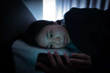 Asian woman on bed late at night and using mobile smartphone before sleep
