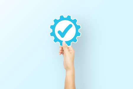 Hand holding paper with icon gear and check mark on light blue background. Concept of Standard quality control certification assurance guarantee