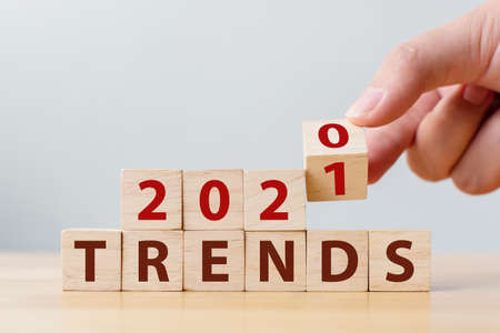2021 trends concept. Hand flip wood cube change year 2020 to 2021 and the word TRENDS on wooden block on wood table