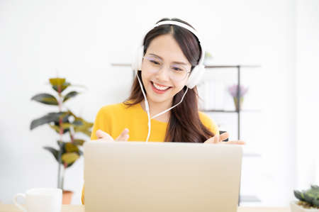 Asian young woman student wear wireless headset video conference calling on laptop computer talk by webcam learn teach in online chat, distance webinar online teaching concept