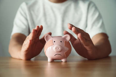 Man hand protect piggy bank on wood table. Save money and financial investment 版權商用圖片