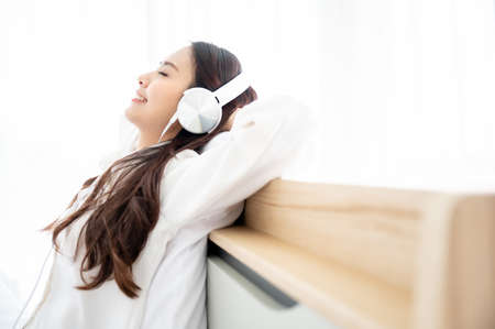 Beautiful young asian woman in headphones listening to music and lying down on bed at bedroom in morning time 版權商用圖片