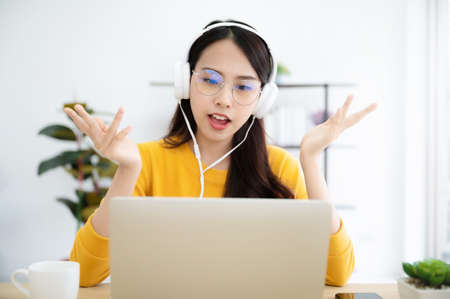 Young asian woman in headphone having conversation chatting while using laptop at house. Work at home, Video conference, Online meeting video call, Virtual meetings, Remote learning and E-learning 写真素材