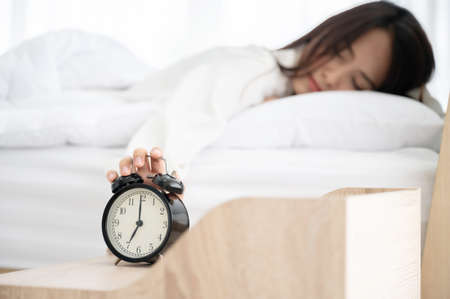 Young asian woman wake up early in morning. She lying on bed and trying turn off alarm clock 写真素材