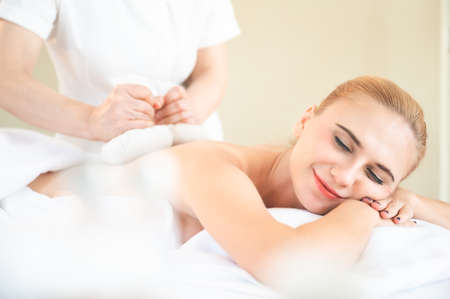 Health care and thai massage. Beautiful woman getting thai herbal ball compress back and shoulder massage in spa salon