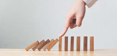 Hand stopping wooden domino business crisis effect or risk protection concept