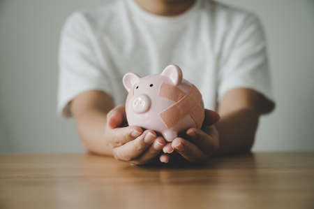 Man hand holding piggy bank on wooden table. Concept of save money and finance business investment 写真素材