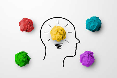 Concept creative idea and innovation. Paper scrap ball yellow colour outstanding different group with light bulb and head human symbol