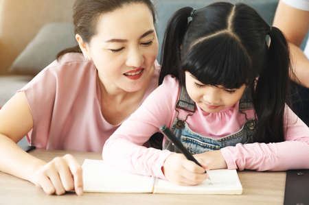 Asian mother helping daughter with homework at living room
