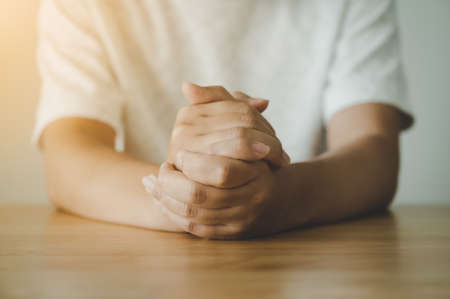 Hand of a man praying hope for better on wood table. Good luck, Success, Forgiveness. Belief of religion