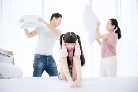 Asian daughter sad and closing her ears while parent quarrelling and fighting in bedroom