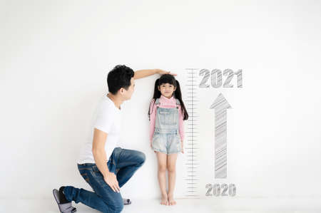 Dad measures height growth of her child daughter at white brick wall with number date year 2020 to 2021