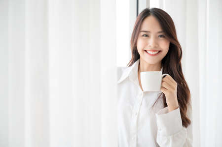 Young asian woman standing beside window and holding mug in bedroom at home, She drinking milk after wake up in the morning Фото со стока
