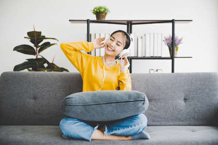 Beautiful young asian woman wearing headphones listening to music and sitting on sofa in living room